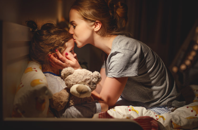 mother puts her daughter to bed and kisses her forehead