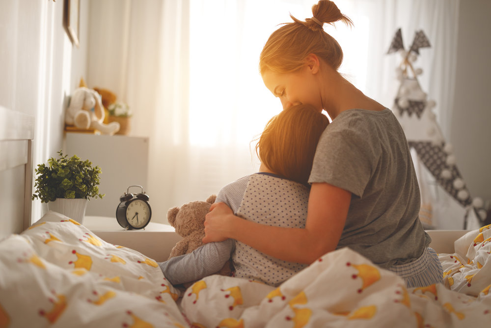 Mother and child hugging on a bed