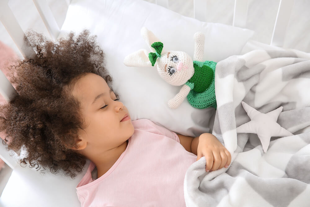 Toddler girl in crib with blanket and stuffed animal