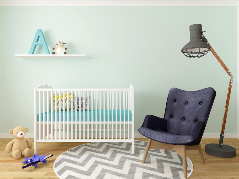 soft green kids room with crib and chair