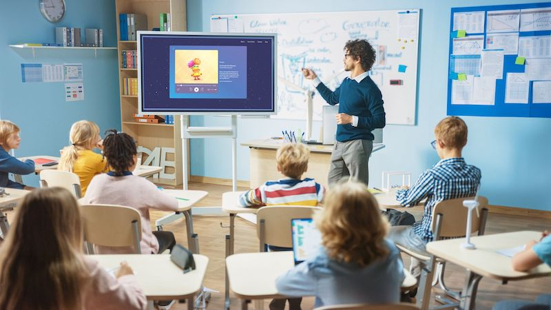 teacher managing classroom with Moshi for schools on the screen